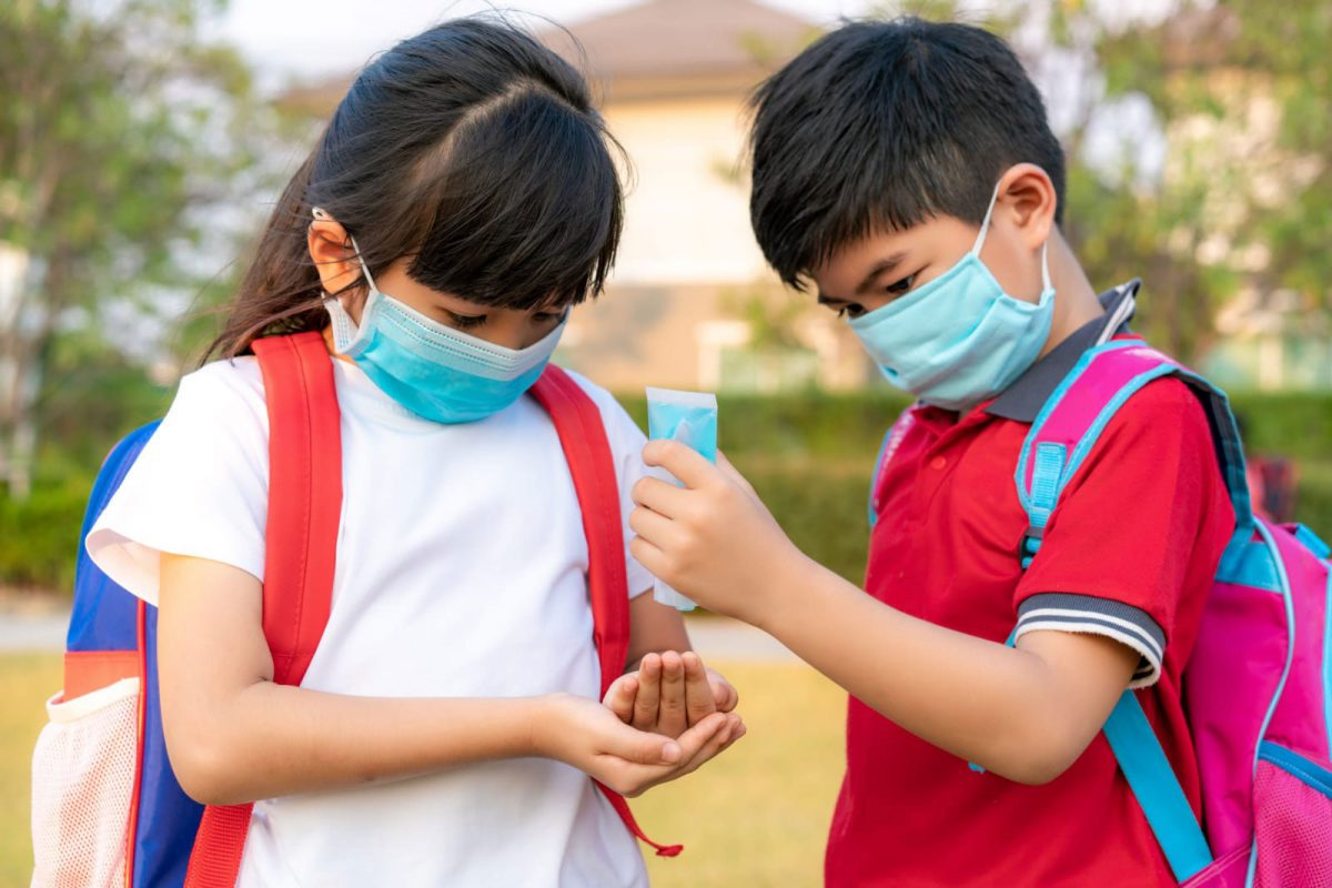 Two children wearing facemasks and using hand sanitiser at SIS International School in Bangladesh.